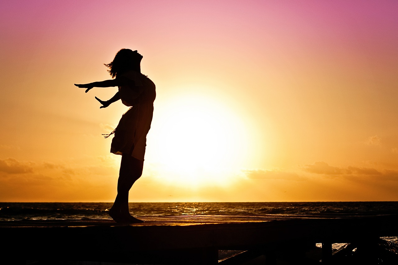 Woman blissful stretch at sunset