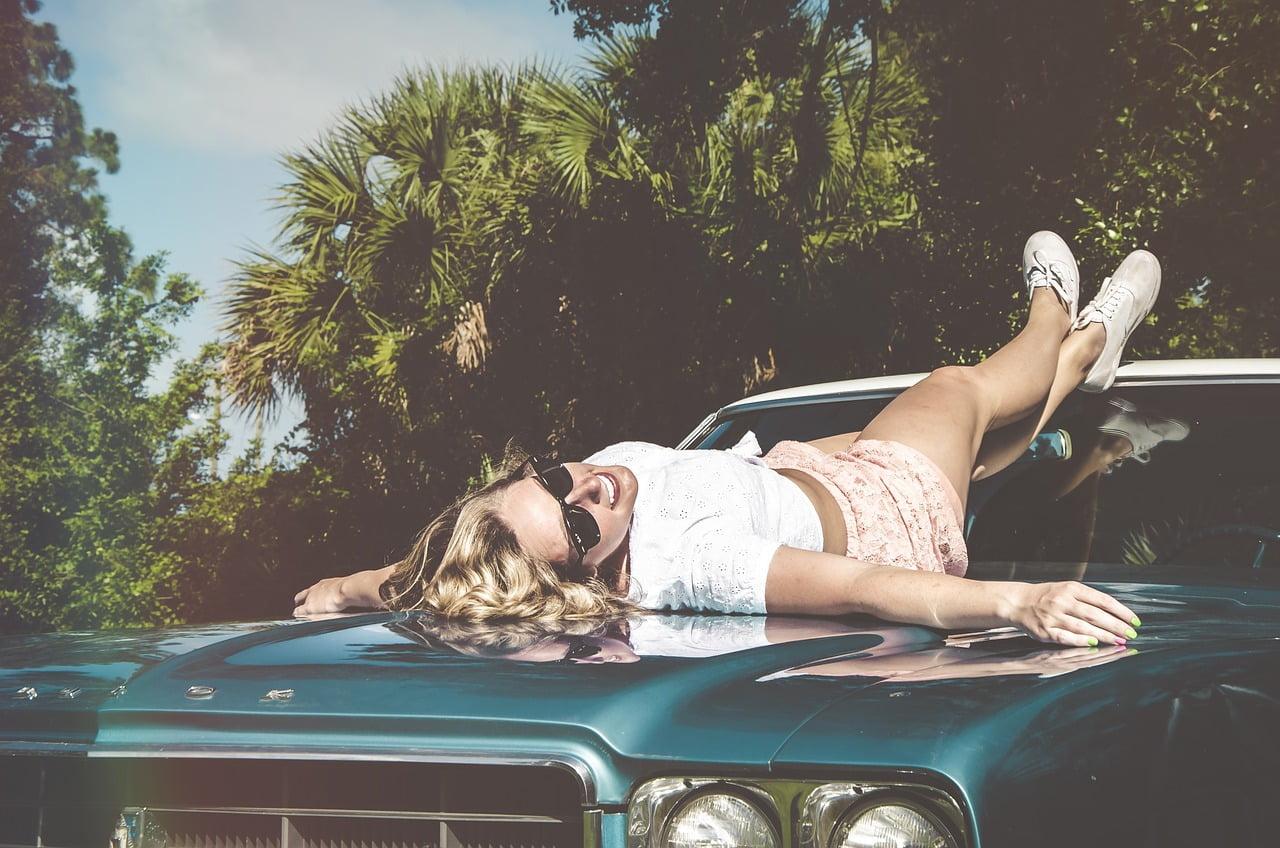 Woman laying on hood of car