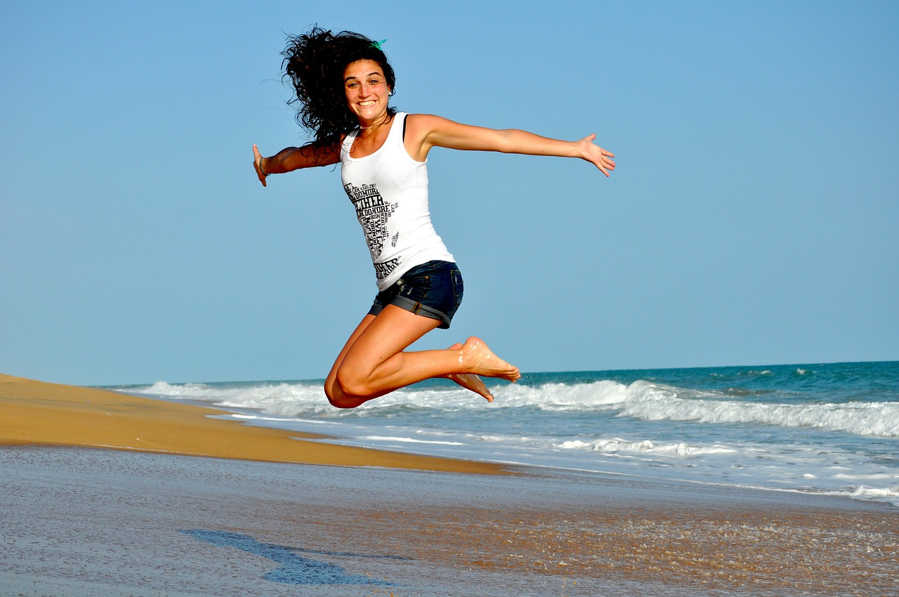 Lady jumping for joy on beach