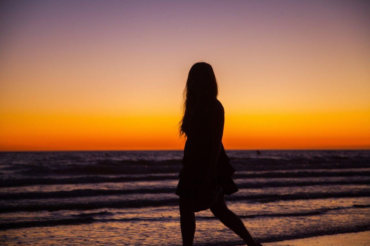 Woman Walking on Beach at Sunset