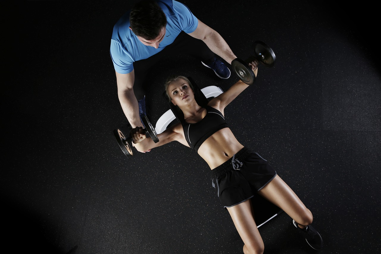 young woman working out with personal trainer