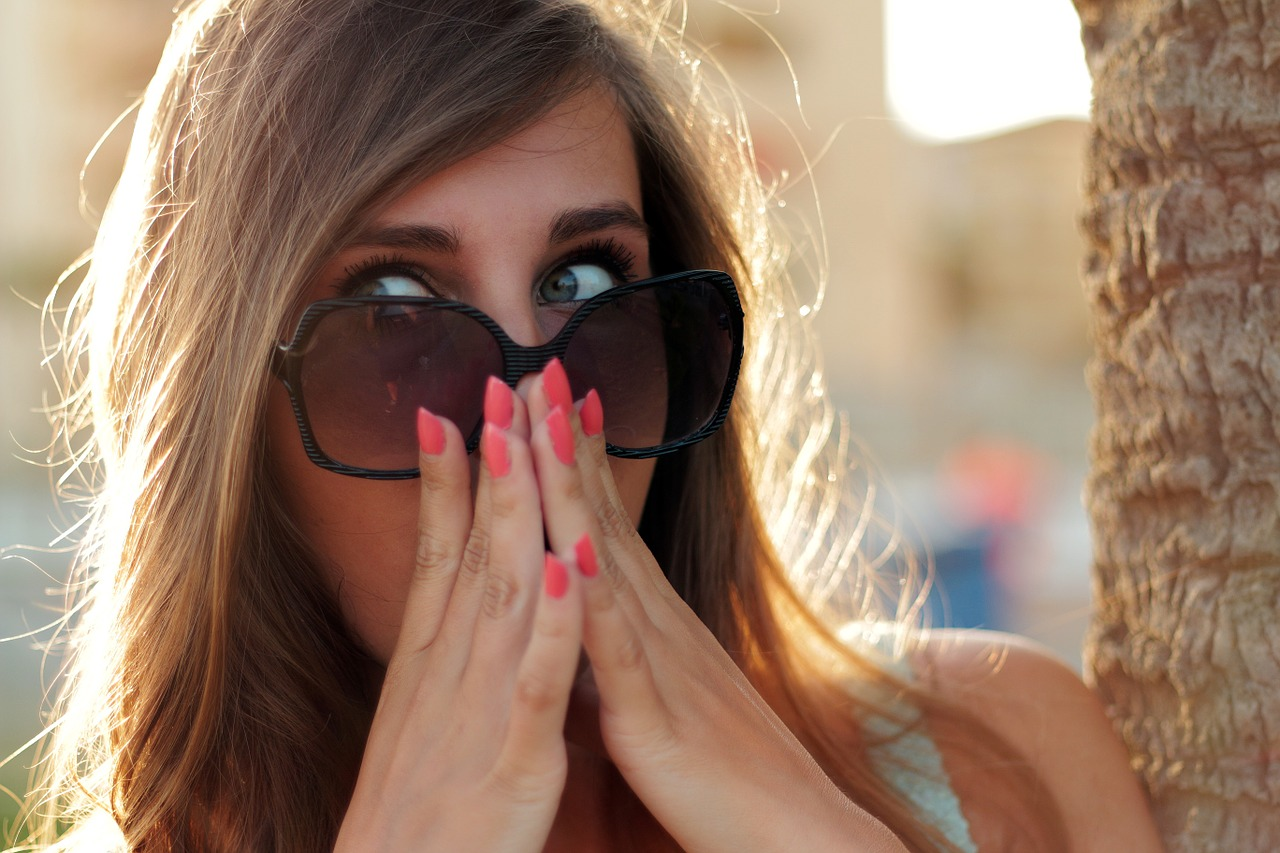 Young lady with sunglasses acting surprised