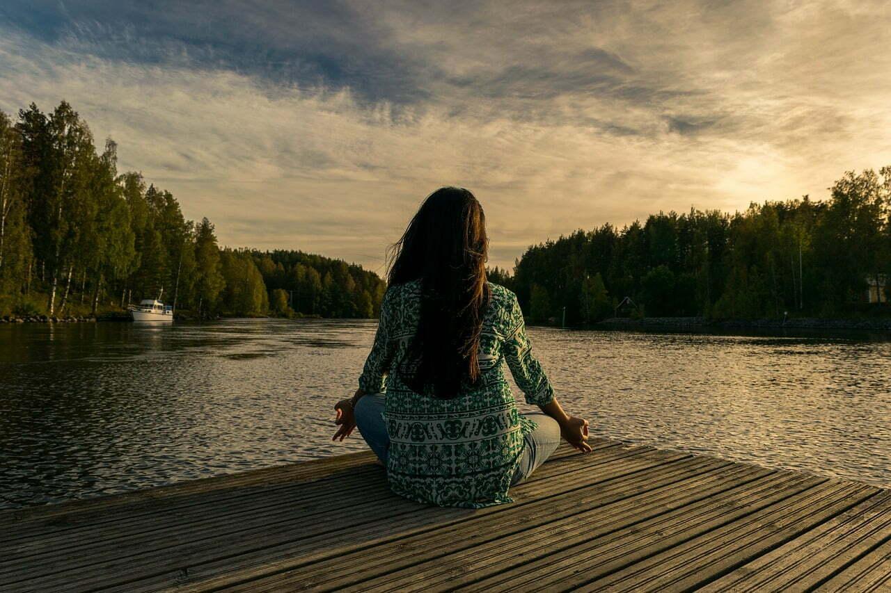 Woman sitting at dock meditating