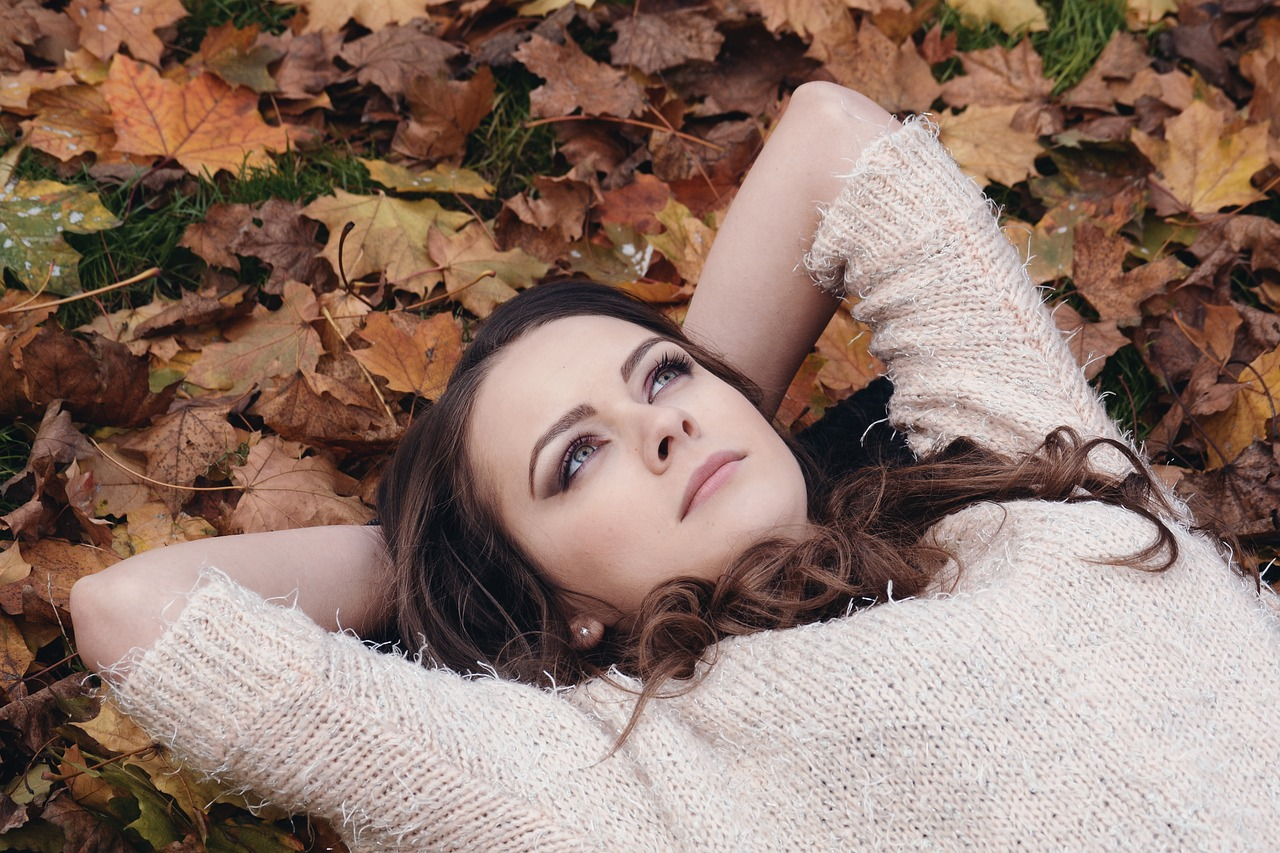 Girl relaxing on fall tree leaves
