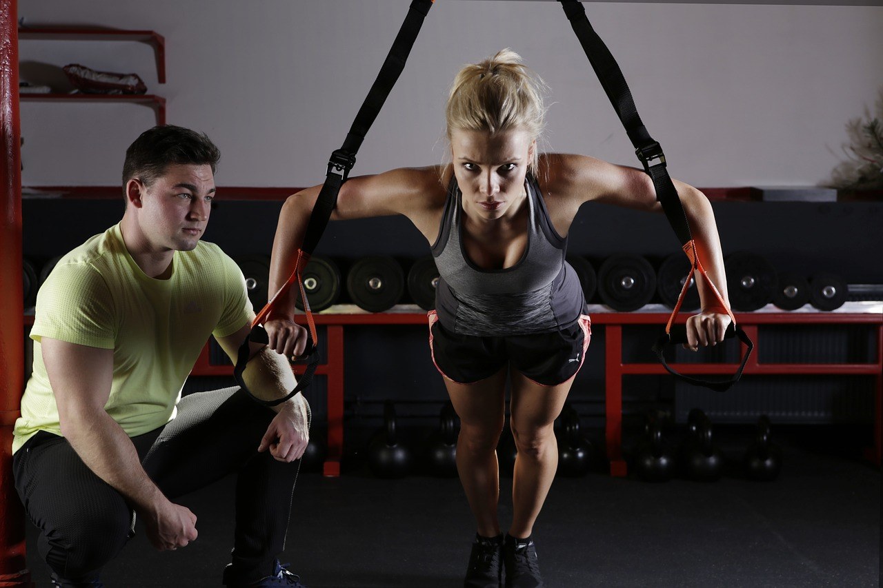 woman cable flies with personal trainer