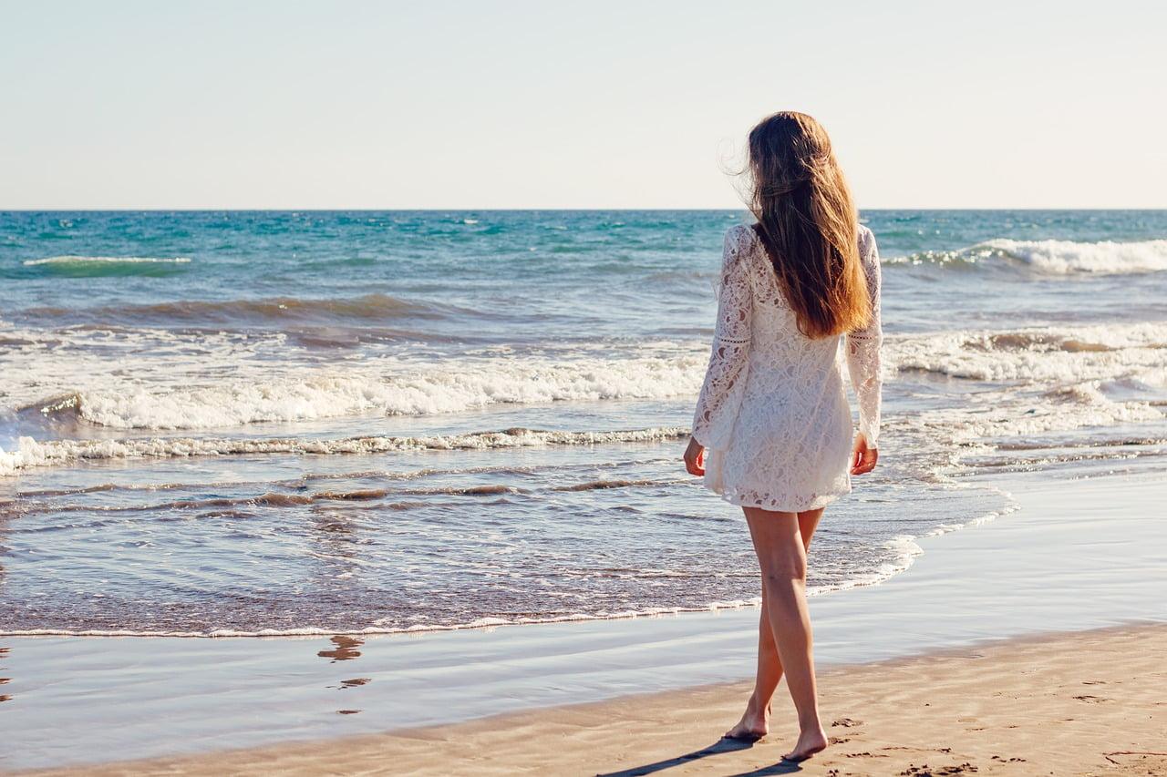 woman white dress walking on beach