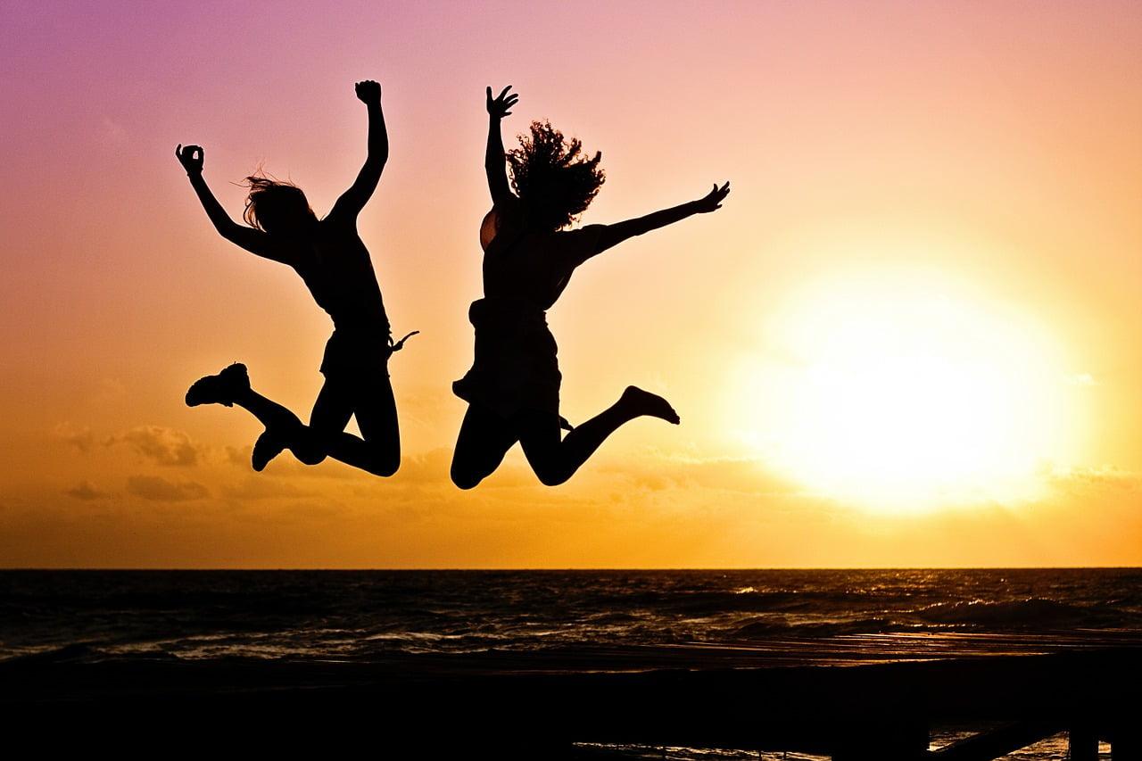 two women jumping sunset beach