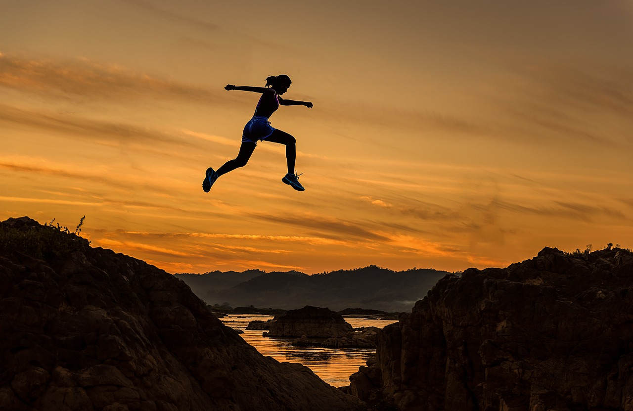 woman jumping sunset