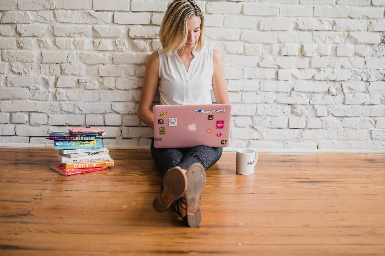 woman on floor on pink laptop