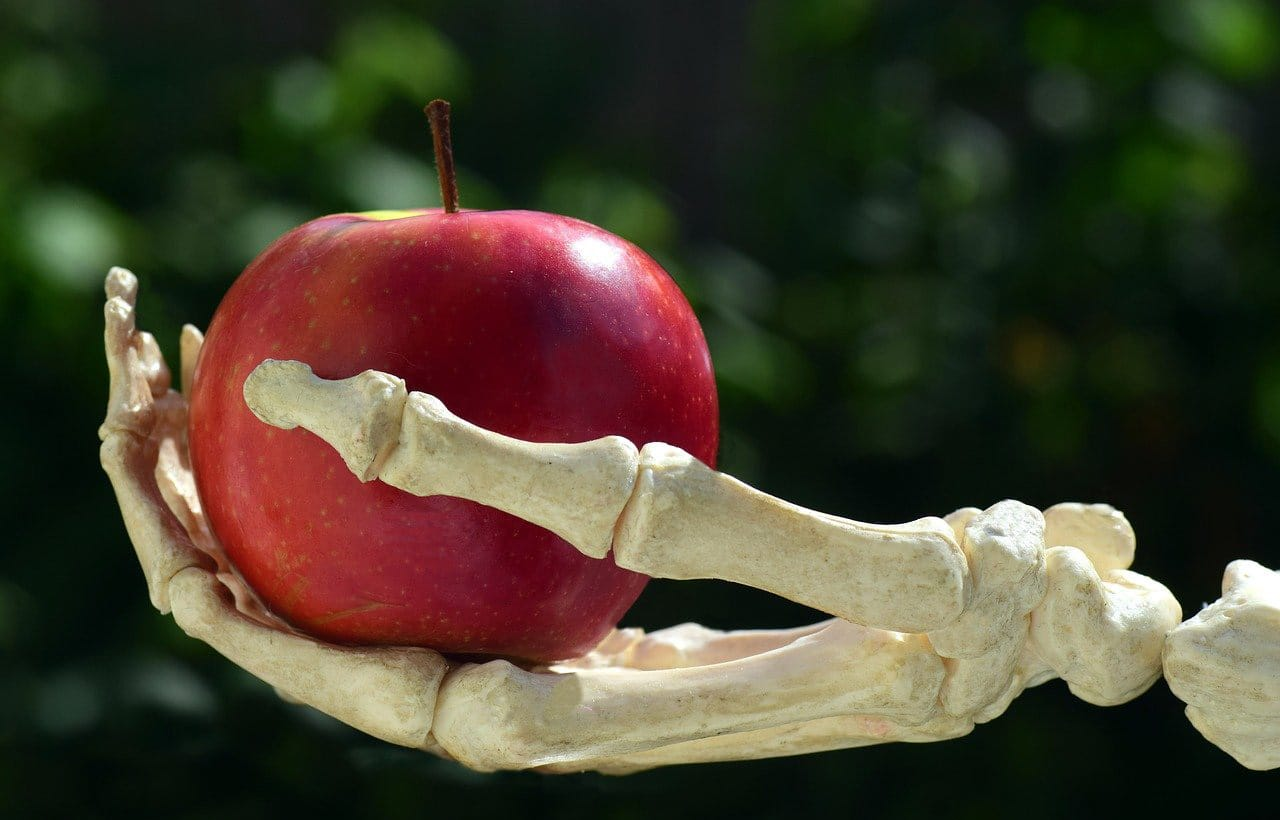 Skeletonn Hand Holding Poisoned Apple