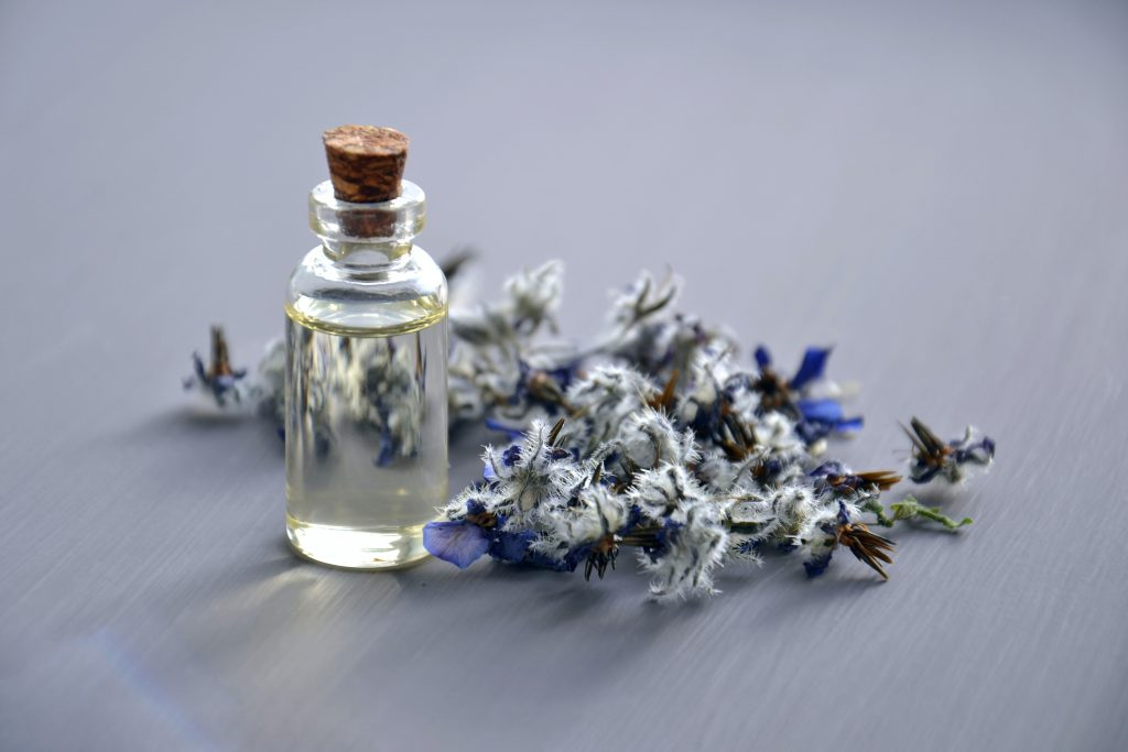 A bottle of lavender oil with flowers