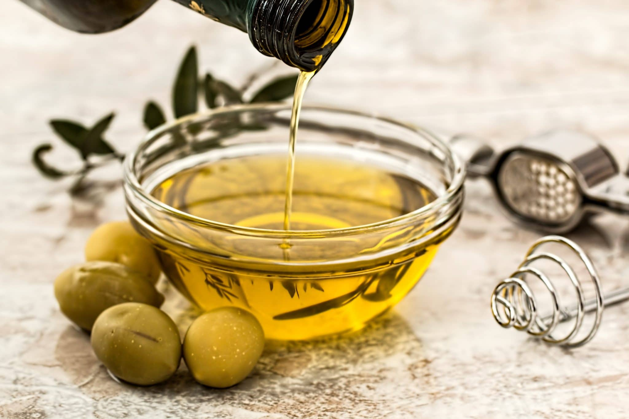 A picture of a bottle pouring olive oil into a bowl