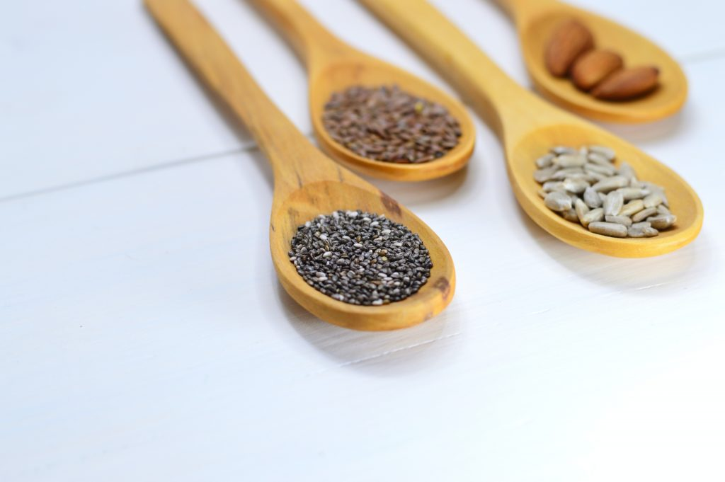 A picture of spoons with different plants seeds