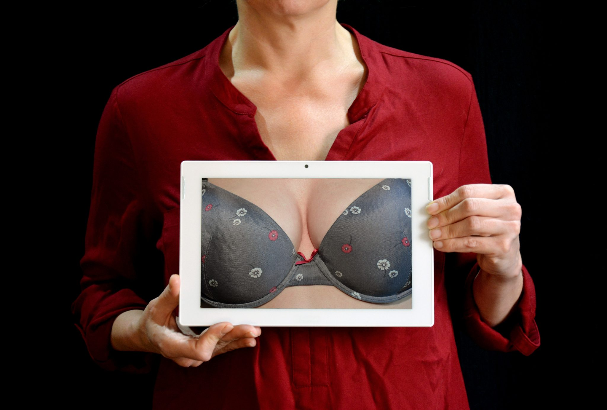 A picture of a woman wearing red and holding a picture of a woman's breast